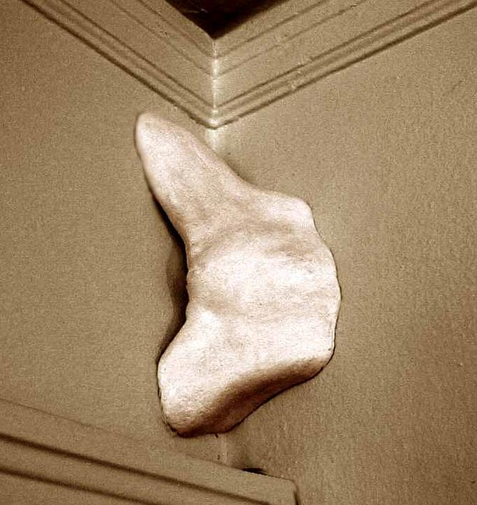 a plaster torso emerges from a room-corner
