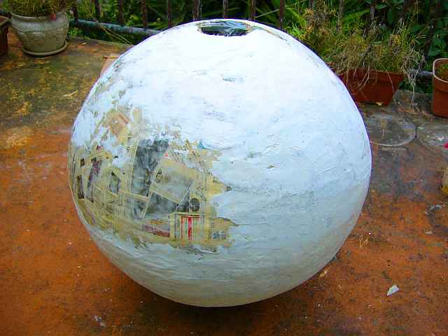 Photo of a big papier-mache egg, mostly white, some newspaper still showing.